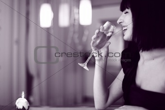 laughing pretty brunette woman in glad rags sitting at a table at the celebration