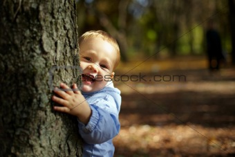beautiful laughing little boy  hiding and peeking from behind a tree