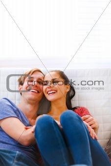 Young couple sitting at couch and laughing