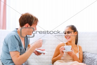 Young couple sitting at couch and drinking coffee