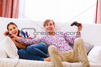 Young man taking joystick from his winning girlfriend while playing console