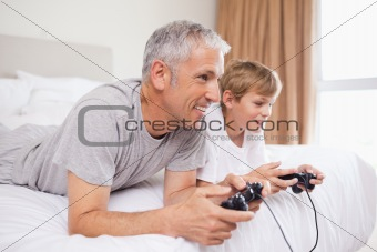 Smiling father and his son playing video games