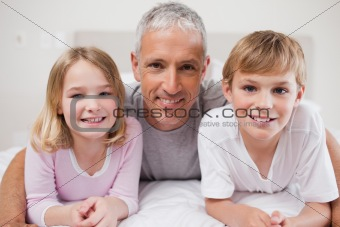Smiling siblings and their father posing