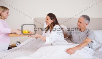 Girl serving breakfast to her parents