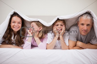 Happy family lying under a duvet