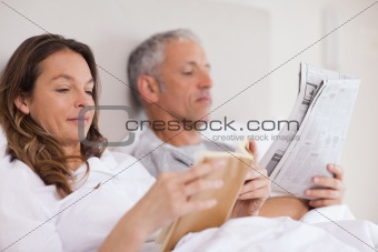 Woman reading a book while her husband is reading the news