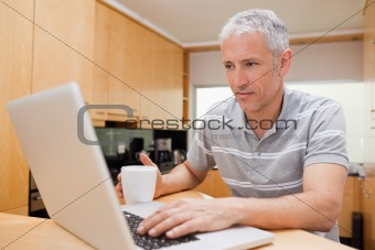 Man using a laptop while drinking coffee