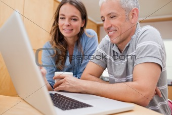 Couple using a laptop while having coffee