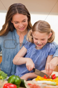 Portrait of a mother slicing bell pepper with her daughter