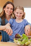 Portrait of a happy mother preparing a salad with her daughter