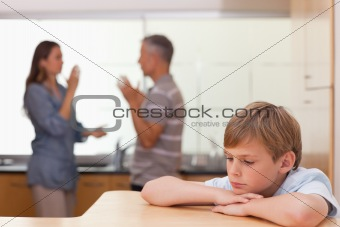 Sad little boy hearing his parents having am argument