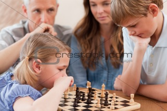 Focused children playing chess in front of their parents