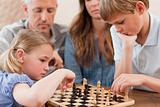 Focused siblings playing chess in front of their parents