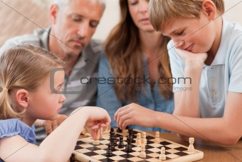 Close up of siblings playing chess in front of their parents
