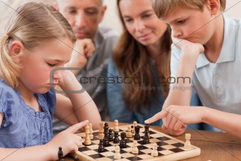 Close up of children playing chess in front of their parents