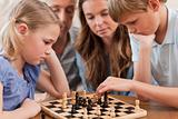 Close up of serious children playing chess in front of their parents