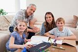 Happy parents helping her children to do their homework