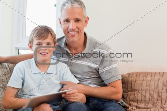 Smiling father and his son using a tablet computer