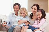 Smiling family watching television together