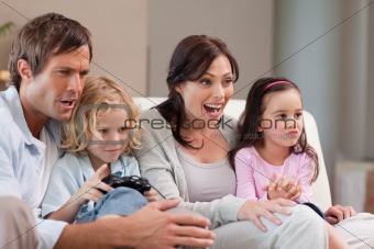 Cheerful family playing video games together
