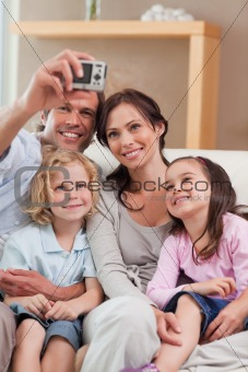 Portrait of a happy father taking a picture of his family