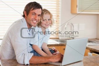 Boy and his father using a notebook together
