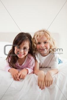 Portrait of siblings lying on their bellies