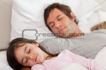 Calm father sleeping with his daughter