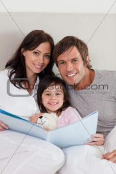 Portrait of parents reading a story to their daughter