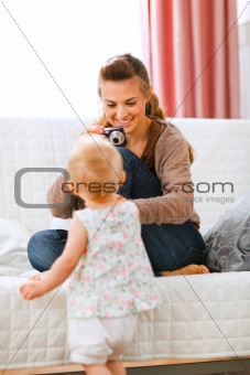 Young mother making photos of baby