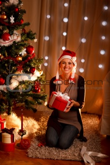 Portrait of pretty girl near Christmas tree holding gift