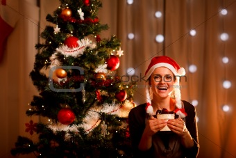 Portrait of smiling young woman near Christmas tree with present box