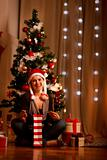 Smiling young woman near Christmas tree opening Christmas present