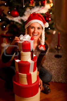 Smiling young woman near Christmas tree looking out from pile of present boxes