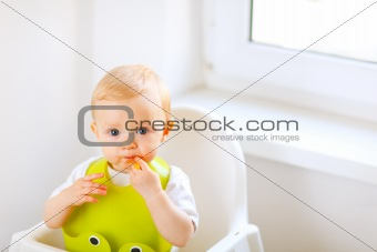 Portrait of eat smeared baby sitting in baby chair