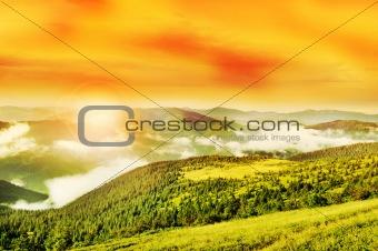 Flaring sun, golden sky and cloudy Carpathian Mountains