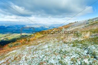 First winter snow and autumn colorful foliage on mountain