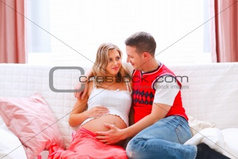 Happy young husband holding his pregnant wifes belly