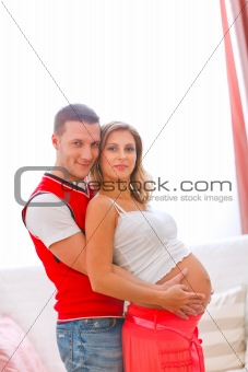Portrait of young pregnant woman with husband hugging her tummy