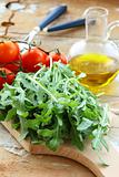 ingredients for the salad tomato and arugula on the kitchen board