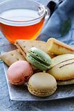 traditional french macarons with tea set on the background