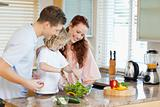 Couple letting their child stir the salad
