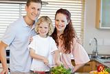 Smiling family preparing salad together
