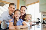 Family standing together behind the kitchen counter