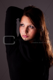 Young and attractive woman looking up, with hands holding hair, studio shot