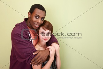 Mixed race teen couple lovingly hug in front of green wall