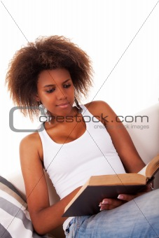 beautiful woman black reading, on couch, with headphones, isolated on white, studio shot