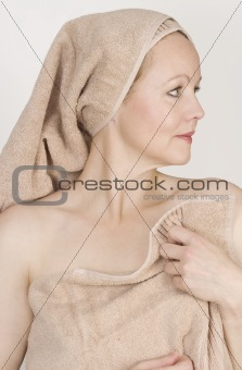 Adult beautiful woman after bath with a towel on her head.