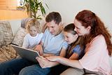 Family using notebook on the sofa