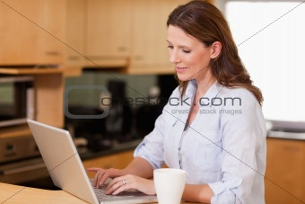 Woman in the kitchen using her laptop
